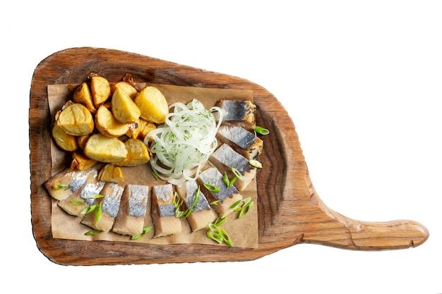 Arenque com batatas e cebolas em uma placa de madeira