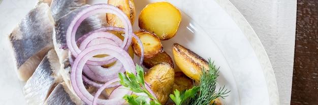 Arenque com batatas fritas e cebolas roxas em um prato branco com fatias de peixe fatias de batatas fatias de filé de peixe decorado com cebola e salsa aperitivos mediterrâneos vista superior web banner