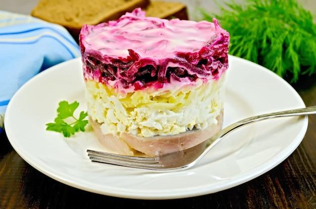 Arenque com legumes e ovo em um prato branco com um garfo, salsa, endro, pão, guardanapo em uma placa de madeira