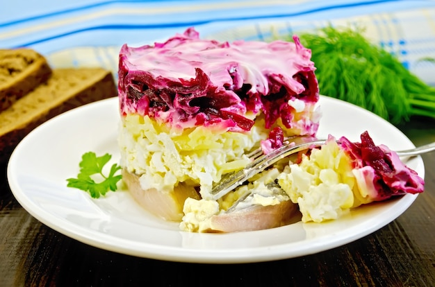 Arenque com legumes e ovo em um prato com um garfo, salsa, endro, pão, guardanapo no fundo de tábuas de madeira