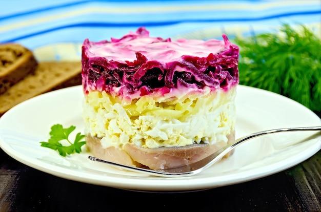 Arenque com legumes em prato branco com garfo, salsa, endro, pão, guardanapo em uma placa de madeira