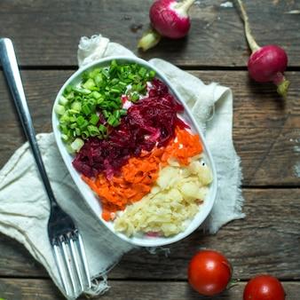 Arenque de salada de vista lateral sob um casaco de pele com tomates e rabanetes