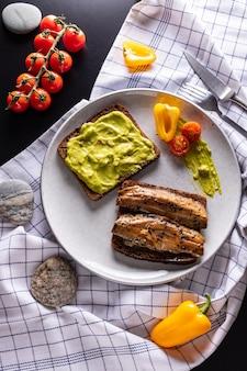 Arenque defumado caseiro e sanduíches abertos de abacate com pão de centeio no prato cinza claro, vista superior