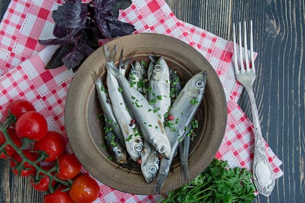 Arenque do mar báltico. peixe arenque salgado em uma tigela com especiarias e ervas.