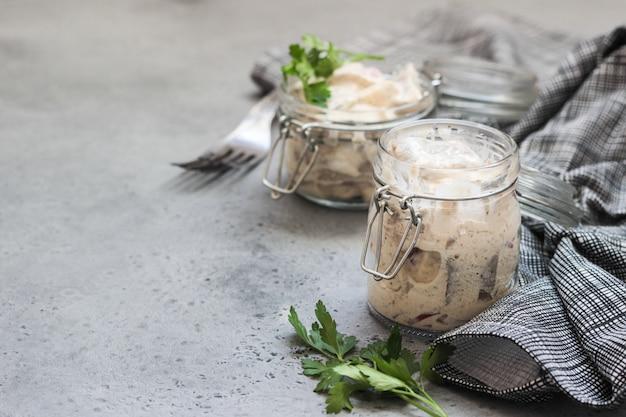 Arenque fatiado em molho de creme de leite, servido em uma jarra de vidro.