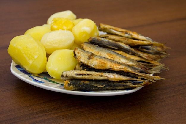 Arenque frito com batatas cozidas num prato fundo de madeira
