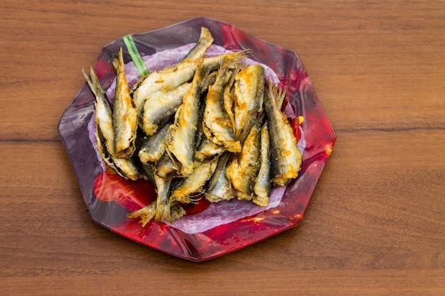 Arenque frito em um prato fundo de madeira