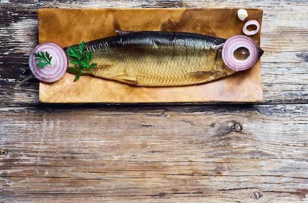 Arenque fumado na vista superior de uma placa de madeira, fundo escuro de madeira com espaço de cópia. ingredientes para fazer um sanduíche de arenque, conceito de comida saudável.