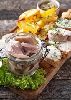 Arenque marinado com cebola em uma jarra