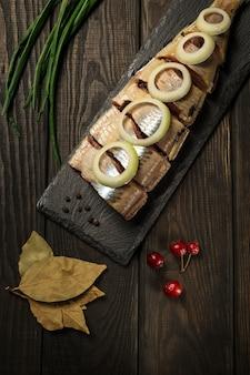 Arenque norueguês cru com cebola e especiarias em um close-up da tábua de servir.