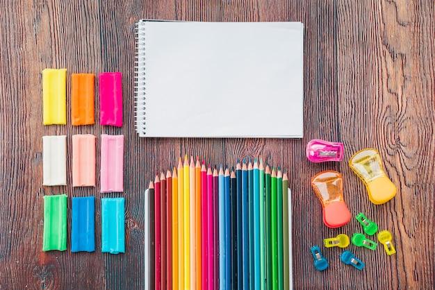 Argila colorida e lápis com bloco de notas em espiral branco na mesa de madeira