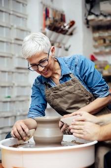 Argila de fiação mulher sênior em uma roda com o professor na aula de cerâmica