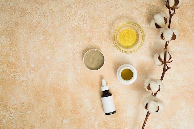 Argila de rhassoul; mel e óleos essenciais com galho de algodão sobre o pano de fundo bege texturizado