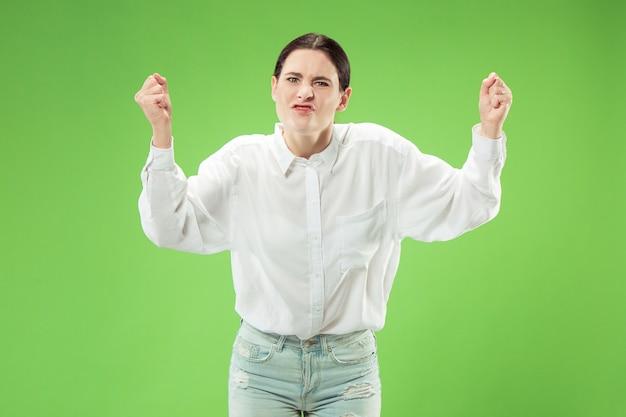 Argumente, discutindo o conceito. belo retrato feminino com metade do comprimento isolado no estúdio verde backgroud. jovem mulher emocionalmente surpresa olhando para a câmera. emoções humanas, conceito de expressão facial
