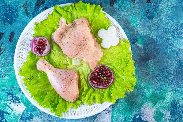 Arilos de romã, folhas de alface com anel de cebola ao lado de carne de frango em um prato