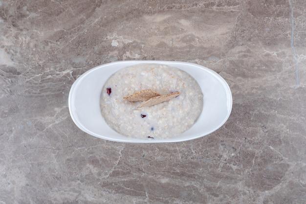 Arilos de romã no mingau no prato, na superfície do mármore