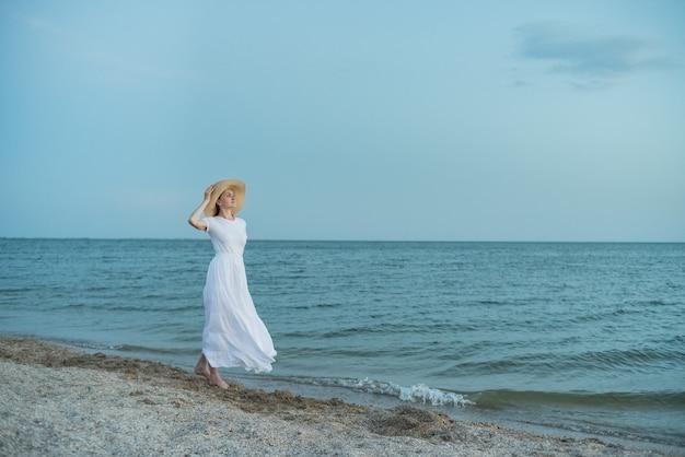 Aristocrata mulher de vestido branco longo caminha na praia. férias náuticas