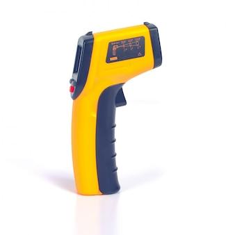 Arma amarela do termômetro infravermelho usada para medir a temperatura no branco.