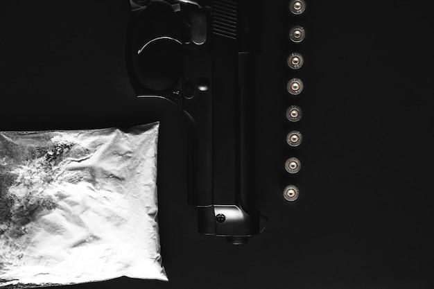 Arma com balas em cima da mesa. problemas criminais. drogas e em fundo preto. venda ilegal.