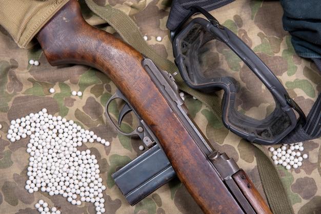Arma de airsoft com óculos de proteção e muitas balas