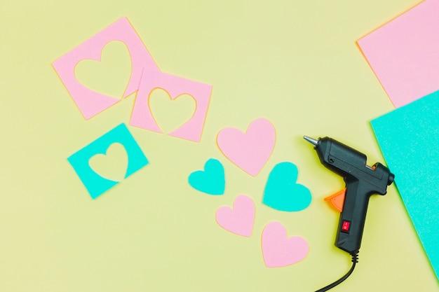 Arma de cola e cortar a forma de coração azul e rosa de papel em fundo amarelo