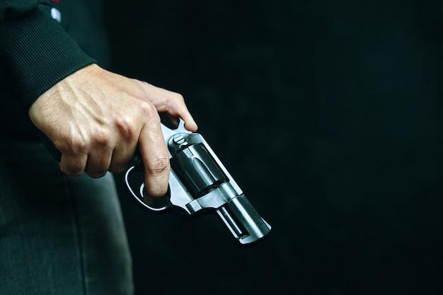 Arma de fogo na mão do homem criminoso com revólver em defesa de fundo escuro ou assassino de ataque ou armado.