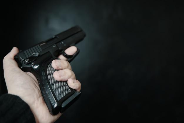 Arma de fogo na mão do homem, visão em primeira pessoa do criminoso armado com pistola na defesa de fundo preto ou ...