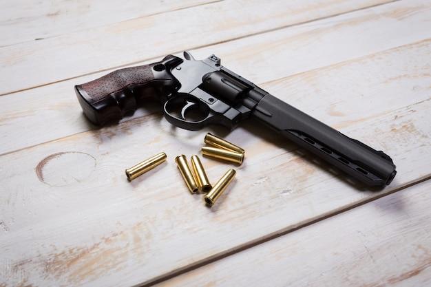 Arma de mão com rodadas na mesa de madeira