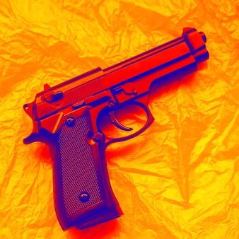Arma deitada em fundo laranja. legalização de arma. conceito de crime.