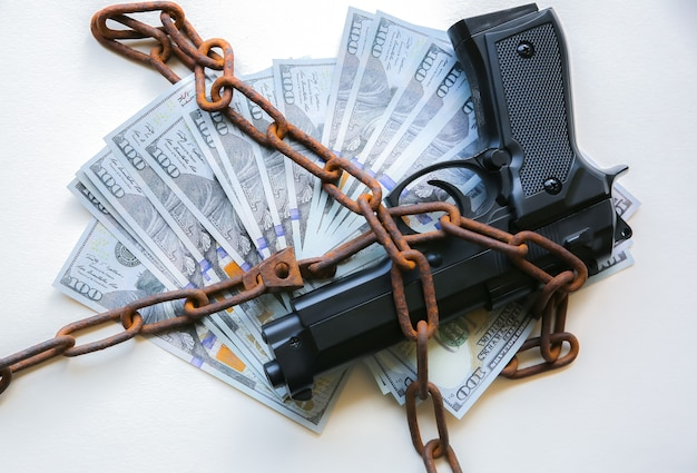 Arma e dinheiro em velhas correntes enferrujadas. preso por crime ilegal. quebrou a lei. conceito criminoso.