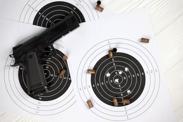 Arma e muitas balas atirando em alvos na mesa branca no polígono de campo de tiro.
