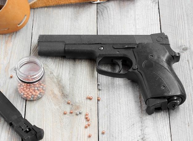 Arma pneumática (gás), revista, coldre e bolas para atirar em uma mesa de madeira.