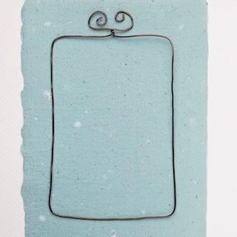 Armação de arame retangular em papel azul contra o pano de fundo branco