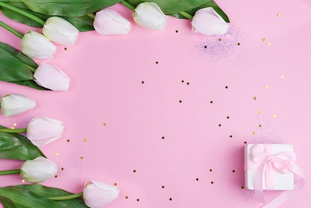Armação de borda com tulipas cor de rosa e caixa de presente em fundo rosa estrelas, cópia espaço