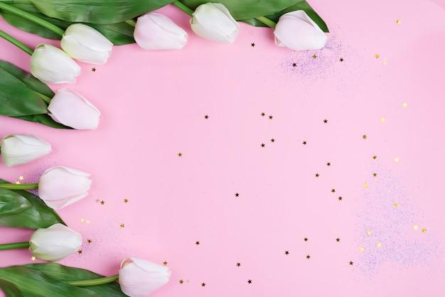 Armação de borda com tulipas cor de rosa em fundo rosa estrelas, cópia espaço