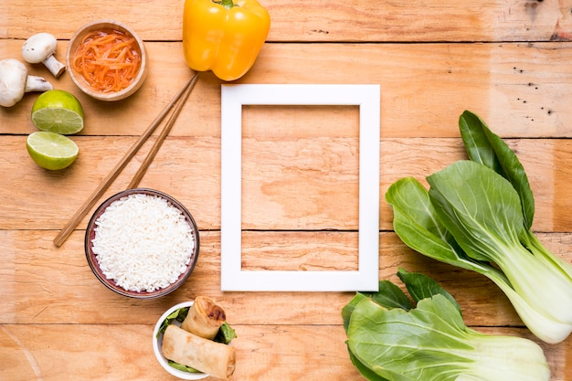 Armação de borda vazia branca com pimentão; bokchoy; arroz; limão; cogumelo e cenoura na mesa de madeira