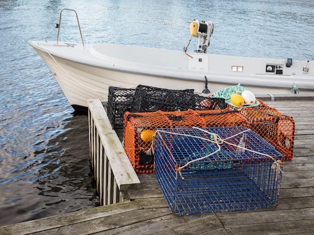 Armadilhas para lagosta e caranguejo em pé em um píer ao lado de um pequeno barco
