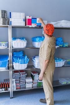Armário com prateleiras de diversos equipamentos e suprimentos médicos de um hospital. sanitizer. prateleiras estocadas de uniformes médicos. o assistente escolhe as coisas.
