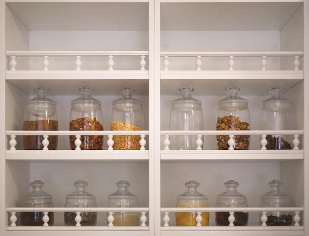 Armário de cozinha com prateleiras abertas onde há potes de vidro com especiarias