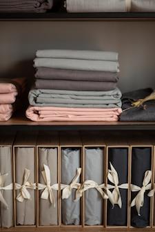 Armário de madeira com roupa de cama e roupas em casa ou em uma loja, conceito de design no interior