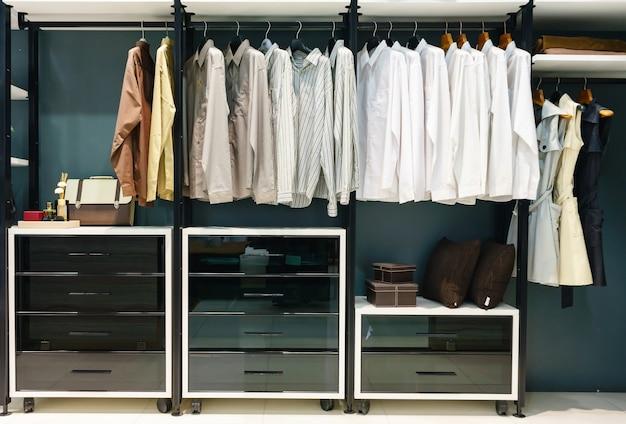 Armário de madeira em pé no armário com roupas penduradas no trilho