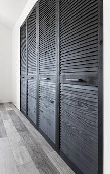 Armário de madeira preta decorado com persianas, armário com decoração de persianas.