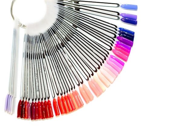 Armário de manicure, esmalte gel em um salão de beleza para uma menina. conjunto de cores diferentes de esmaltes na paleta na loja de cosméticos