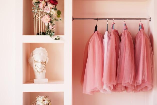Armário de vestir com roupas rosa é organizado em cabides. o guarda-roupa está cheio de saias rosa, acessórios nas prateleiras.