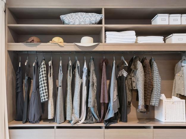 Armário moderno com a fileira do vestido que pendura no gancho de revestimento no vestuário.