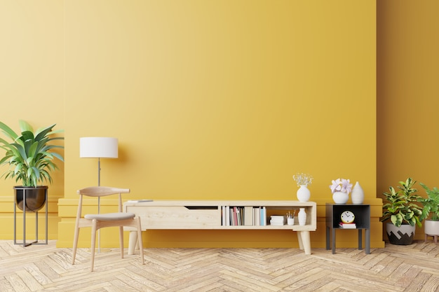 Armário para tv na moderna sala de estar com lâmpada, mesa, flores e plantas na parede amarela