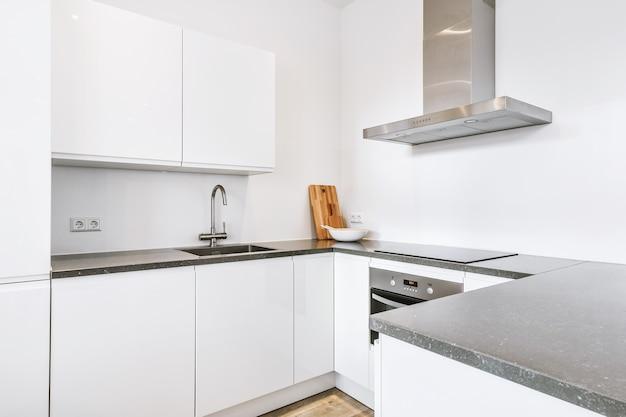 Armários brancos simples com pia e eletrodomésticos localizados sob o exaustor na cozinha moderna de casa