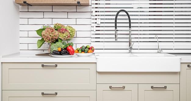 Armários de cozinha brancos com puxadores de metal nas portas junto ao lavatório com um ramo de flores e um prato de legumes.