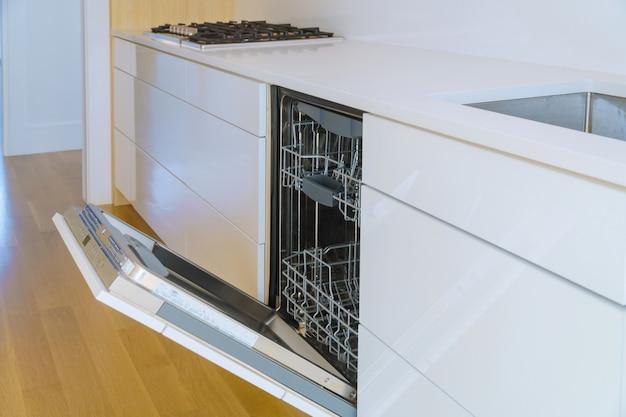 Armários domésticos modernos com novos aparelhos de lavar louça na cozinha