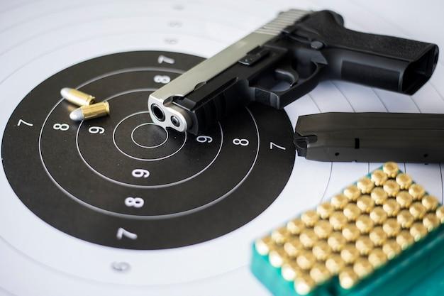 Armas com munição na prática de tiro ao alvo em papel
